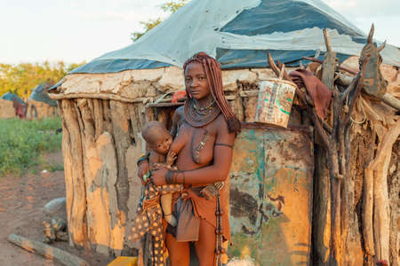 NAMIBIA, OMUSATI REGION, MAY 6: Himba people in village with their daily activities, woman nursing their child. Himba are indigenous namibian ethnic people, in northern Namibia, May 6, 2018, Namibia
