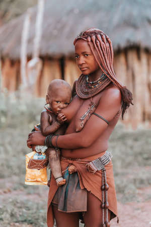 NAMIBIA, OMUSATI REGION, MAY 6: Beautiful and happy Himba woman nursing their child. The Himba are indigenous namibian ethnic people, in northern Namibia, May 6, 2018, Namibia
