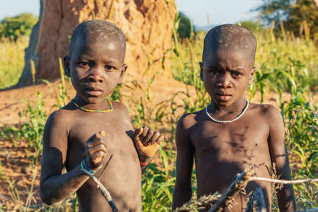 NAMIBIA, OMUSATI REGION, MAY 6: The Himba boys playing at the termite mound. The Himbas are african indigenous namibian ethnic people, in northern Namibia, May 6, 2018, Namibia Africa