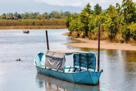 old rusted abandoned boat moored in a lagoon on a river in Maroantsetra, Madagascar. Rural countryside scene.