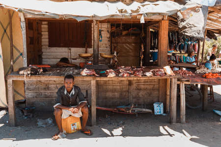 MAROANTSETRA ,MADAGASCAR OCTOBER 18.2016 Malagasy marketplace on main street of Maroantsetra city, local man sell carcass meat in butchery. Daily life on street. Madagascar, October 18. 2016