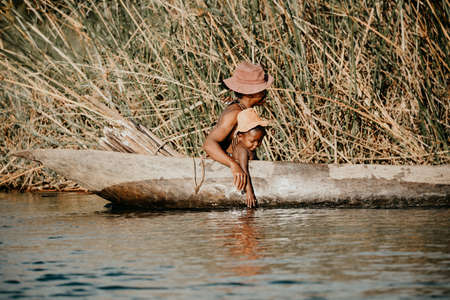 MADAGASCAR OCTOBER 18.2016 Malagasy woman with children from village transport freight by Traditional handmade dugout wooden boat. Daily life on the river. Maroantsetra October 18. 2016, Madagascar. Editorial