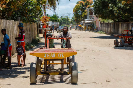 MAROANTSETRA ,MADAGASCAR OCTOBER 18.2016 Malagasy workers transport goods on main street of Maroantsetra city. Madagascar, October 18. 2016