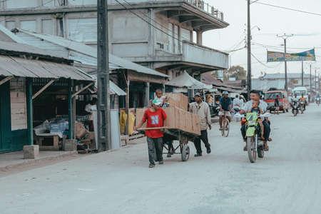 MADAGASCAR OCTOBER 18.2016 Malagasy man pushing a fully loaded wagon on the main street of Maroantsetra. October 18. 2016, Madagascar, Toamasina Province