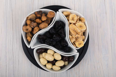 Mix of dried fruits and nuts on a wood background. Symbols of christmas holiday. Reklamní fotografie - 137800400