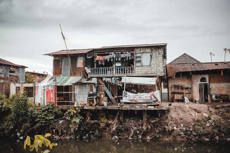 MANADO, NORTH SULAWESI, INDONESIA - AUGUST 3, 2015: View of a ghetto by a river with pollution, the poorest part of Manado city, on August 3, 2015 in Manado, North Sulawesi, Indonesia Editorial