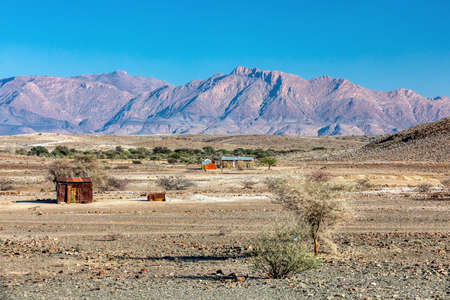 Traditional african hut from rusty sheet of tin in desert of Erongo Region. In background is Brandberg mountain. Namibia wilderness, there living people