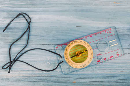 old transparent plastic sport compass with azimuth measurement on wooden background Stock Photo