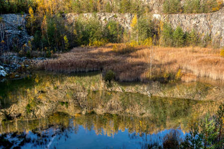 Beautiful reflection of autumn colored trees in water, landscape of abandoned and flooded s, all quarry, Czech Republic