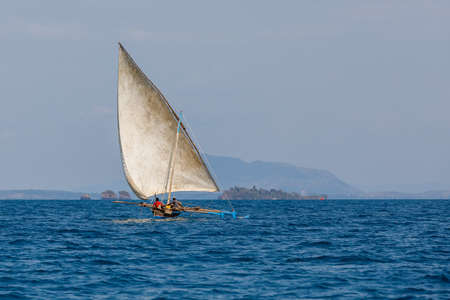 Malagasy fisher man on sea in traditional handmade dugout wooden sailing boat. Everyday life on Nosy be island. Nosy be, Madagascar Фото со стока