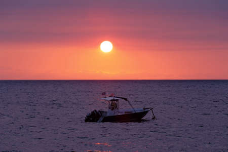 Sunset over indian ocean, Madagascar Nosy be beach with boat silhouette. Travel Africa for vacation concept.