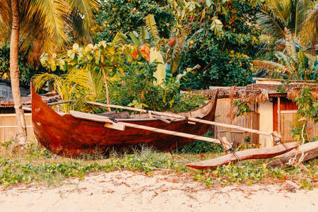 Aboriginal Malagasy wooden hand made fisherman dugout catamaran boat on the beach in Nosy Be, Indian ocean, Madagascar scenery Редакционное