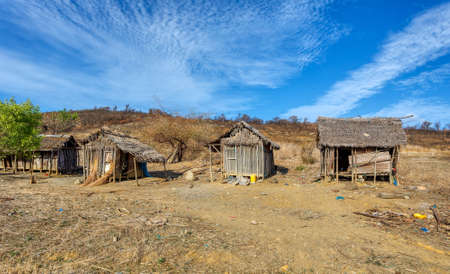 Traditional wooden african malagasy hut with roof from straw, typical village in north west Madagascar. Madagascar landscape. Редакционное