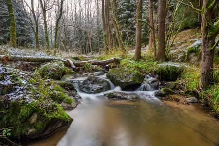 cascade on the small mountain creek in a woodland, long exposure photo with water like milk Banco de Imagens