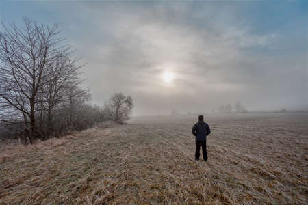 man silhouette walk into the misty foggy countryside in dramatic mystic sunrise scene