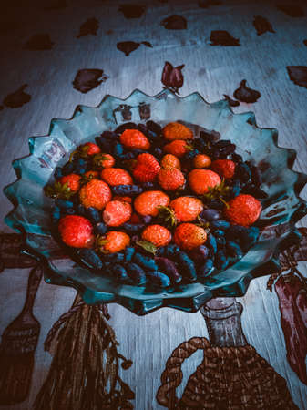 strawberries red and black honeysuckle in a plate Stok Fotoğraf