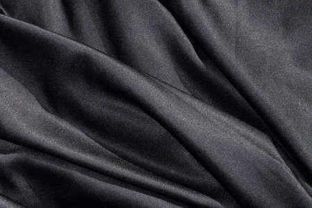 shiny black: background texture of shiny black fabric with pleats