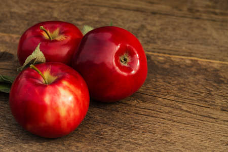 wooden color: apple on a blurred background of apples on a table