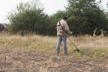 mows: DIKANKA, UKRAINE - SEPTEMBER 30, 2015: Country farmer working mows dry grass trimmer in garden Editorial