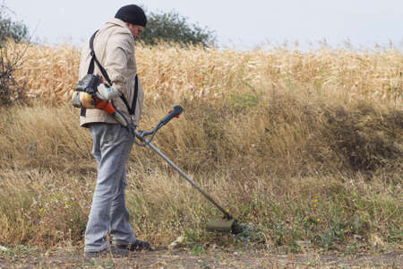 mows: DIKANKA, UKRAINE - SEPTEMBER 30, 2015: Country farmer working mows dry grass trimmer in garden closeup Editorial