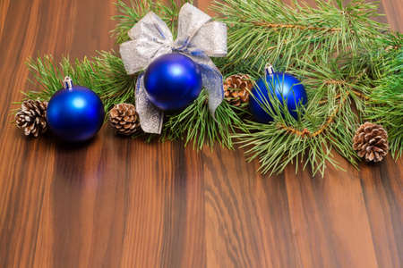festive pine cones: Pine branches with cones and blue Christmas balls with a bow on a wooden background