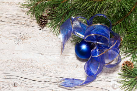 festive pine cones: Pine branches with cones and blue Christmas balls with a bow on a white wooden background