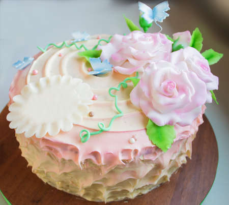 pink  leaf: cream cake with delicate sugar flowers on blurred background. Soft focus.