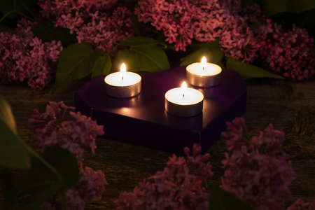 burning bush: Composition of lilac and burning candles on wooden background closeup. dark toned photo. Shallow depth of field. Focus on the center candle.