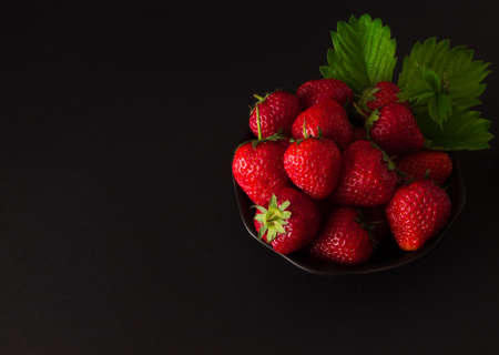 blackout: plate of strawberries with leaves on a black background. Blackout photos.
