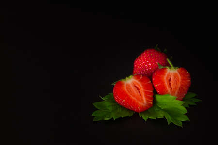 textural: ripe cut in strawberries on a black textural background