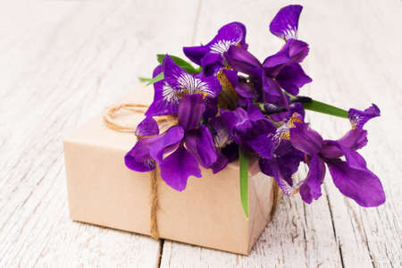 purple irises: bouquet of purple irises flowers and gift closeup on a light wooden background