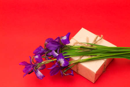 textural: bouquet of purple iris flowers and a box with a gift on a red textural background