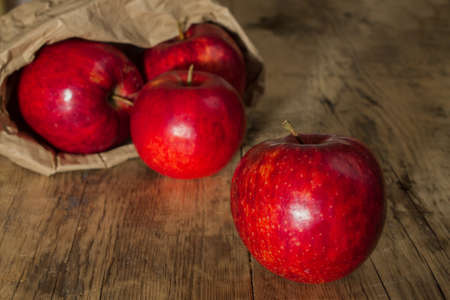 apple paper bag: juicy red apple on a wooden background on a background blur paper bag with apples