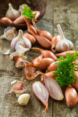 close up of onions in a basket: Scattered from wicker basket of garlic and onions, shallots peeled sliced with green leaves of parsley on a wooden background close-up. Rural scene. Vertical photo