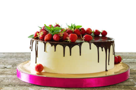 Cake decorated with strawberries and sprinkled with black chocolate on a wooden table on a white background Stock Photo