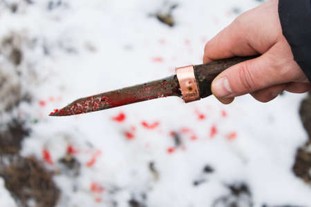 mans hand with a bloody knife close-up on a blurred background