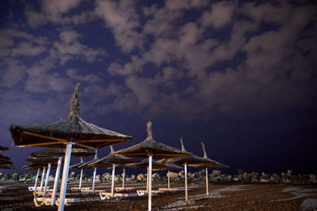 Umbrellas on the beach at night with clouds and stars on the sky