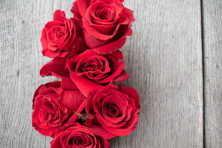 Rode rozen op een rustieke achtergrond. Rozen op een grijze houten ondergrond Stockfoto