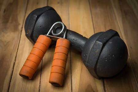 hand gripper: Hand Gripper and dumbbell on wooden