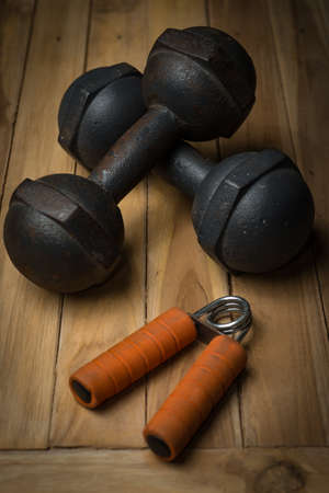 gripper: Hand Gripper and rust dumbbell on wooden