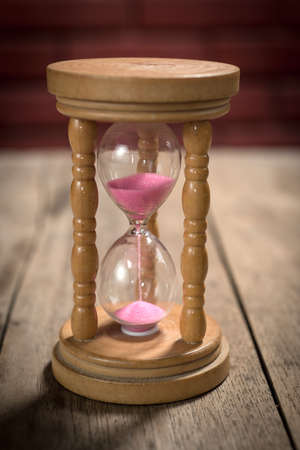 ancient pass: vintage hourglass on wood table Stock Photo