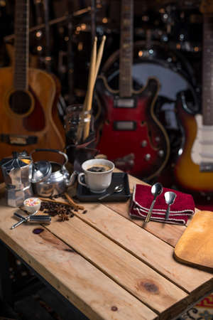 coffee cup on wood table background with musical instrument