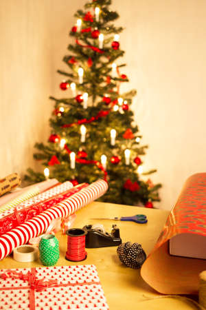 wrapping paper, scissors, tape and ribbon with christmas tree photo