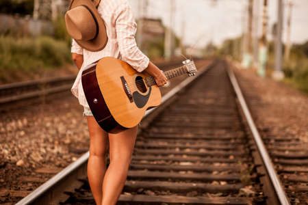 only 1 girl: Girl walks alone the railway with guitar