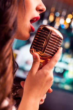 retro microphone: Woman sings in microphone