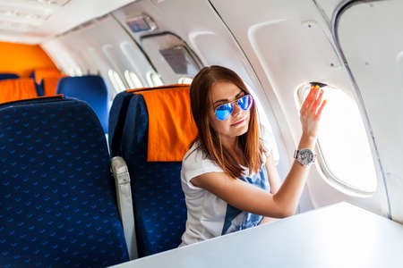 Woman looking at the window of the airplane on the passenger seat