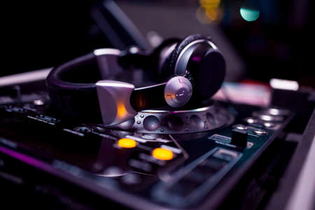 professional headphones on dj board in night club