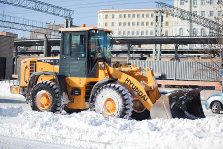 wheel loader: Wheel loader cleaning road from snow in Russia