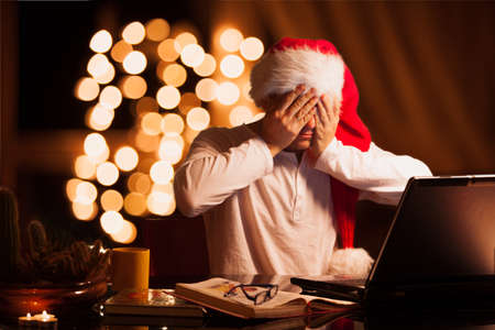 cristmas: Man winks in cristmas hat at the laptop
