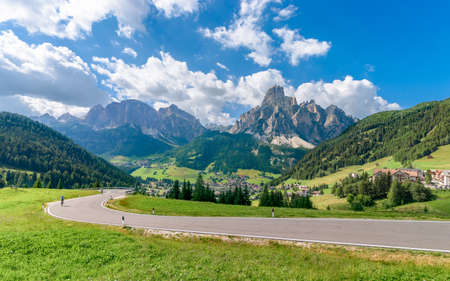 A view of the Italian Alps and the city of Corvara (in the foreground there is a road with two cyclists) Italian Dolomites